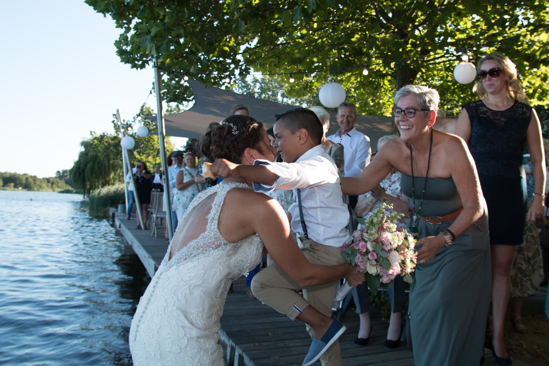 Zoontje omhelst Denise, trouwfoto aankomst bruidspaar